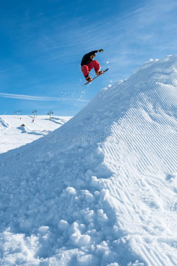 Snowboarder die tegen blauwe hemel springt royalty-vrije stock foto