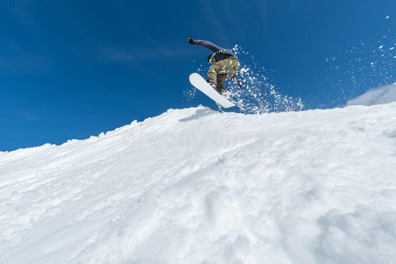 Snowboarder die tegen blauwe hemel springt stock foto