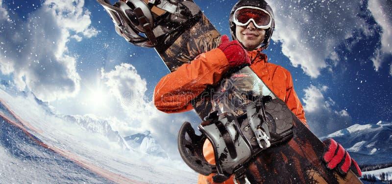 Snowboarder die zijn snowboard houden stock foto's