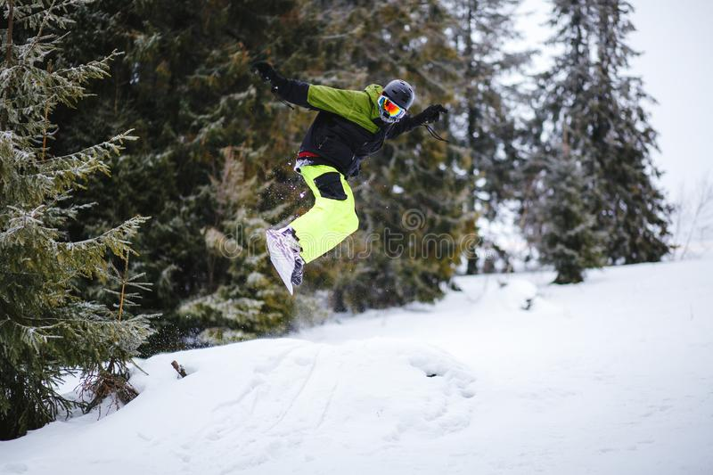 Snowboarder does the trick on the kicker royalty free stock photography
