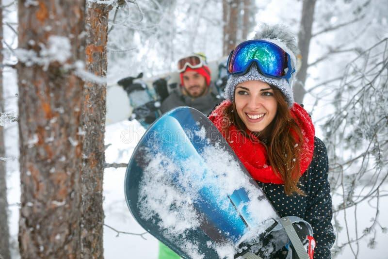 Snowboarder dos amigos que tem o divertimento na floresta do inverno imagens de stock