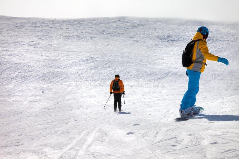 Snowboarder e esquiador para baixo na fora-pista fotografia de stock