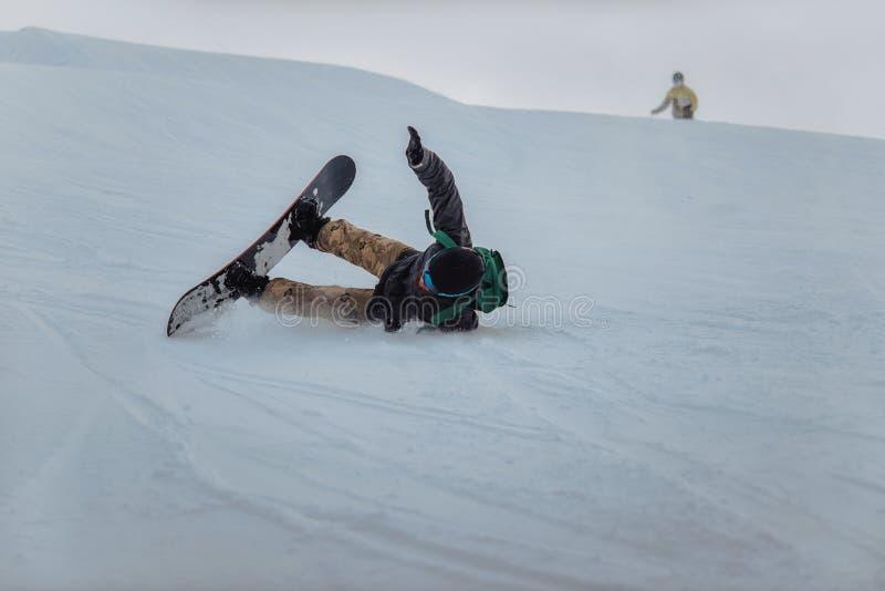 Snowboarder in een zwarte helm die op een sneeuwspoor berijden royalty-vrije stock fotografie