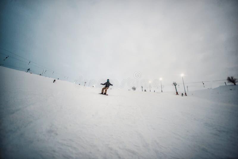 Snowboarder in einem schwarzen Sturzhelmreiten auf einer schneebedeckten Bahn lizenzfreie stockbilder