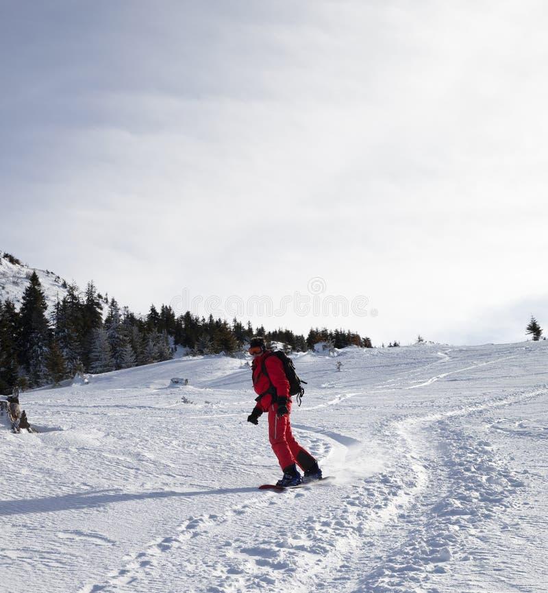 Snowboarder en declive en cuesta fuera de pista nevosa por mañana del invierno imagen de archivo