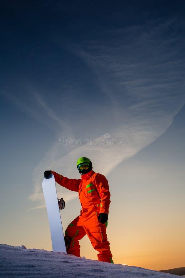 Snowboarder en el top de la cuesta del esquí en el fondo de la puesta del sol hermosa fotos de archivo libres de regalías