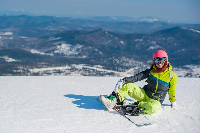 Snowboarder en la ropa amarilla que descansa sobre la montaña fotografía de archivo libre de regalías
