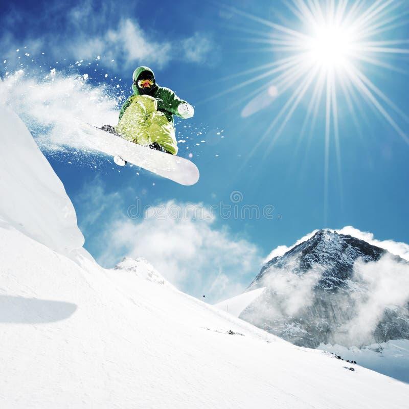 Snowboarder en las montañas del inhigh del salto