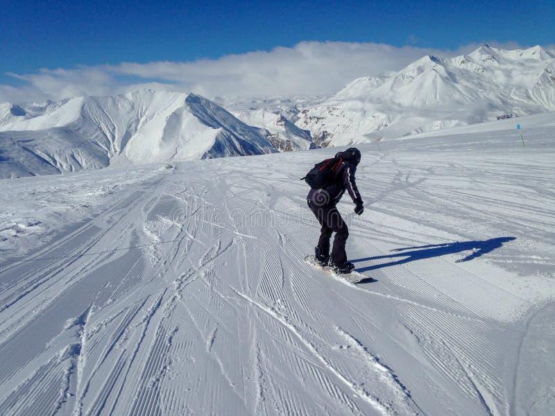 Snowboarder en traje negro a bordo en las montañas nevosas Concepto del deporte de invierno Fondo activo de la forma de vida foto de archivo