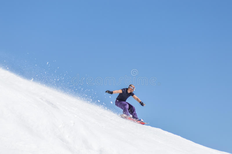 Snowboarder enjoying runs and jumps on spring`s last snow. royalty free stock photography