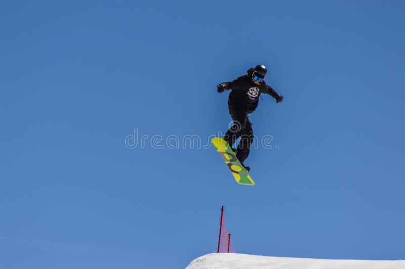Snowboarder enjoying runs and jumps on spring`s last snow. royalty free stock photos