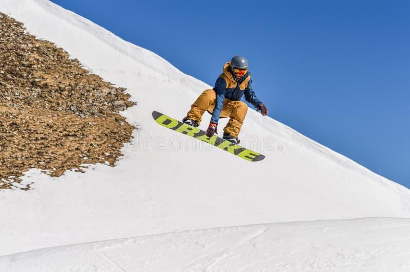 Snowboarder enjoying runs and jumps on spring`s last snow. stock photo