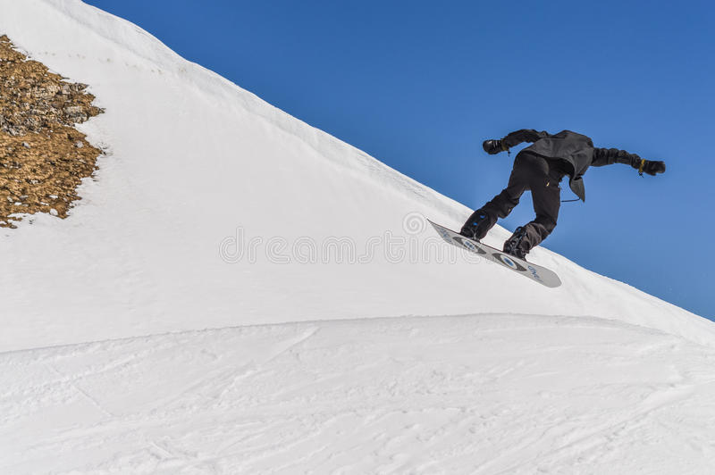 Snowboarder enjoying runs and jumps on spring`s last snow. royalty free stock images