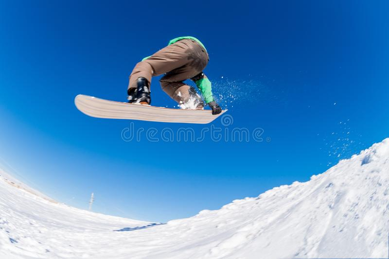 Snowboarder jumping against blue sky. Snowboarder executing a radical jump against blue sky royalty free stock photos