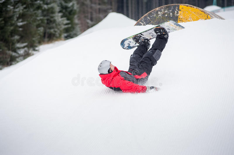 Snowboarder falls on the slopes during the jumping. Snowboarder falls to rate on the slopes during the descent, fresh white snow background in winter day stock photo