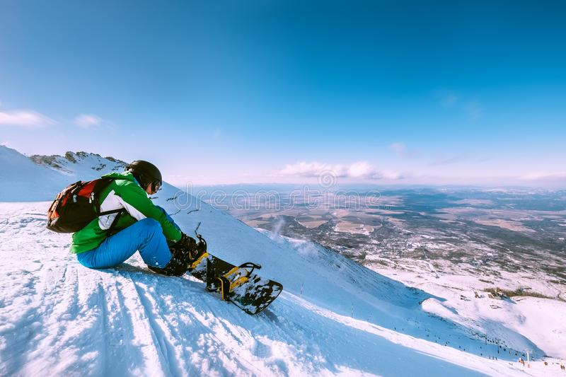 Snowboarder fastens snowboard buckles sitting on the top of snow hill stock photography