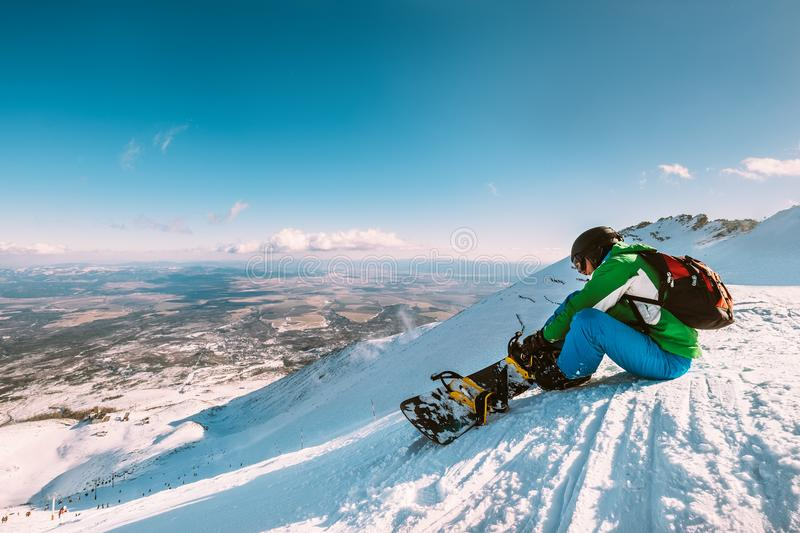 Snowboarder fastens snowboard buckles sitting on the top of snow hill stock images