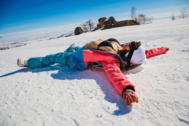 Snowboarder femminile sexy che si trova su lei indietro sulla neve nell'inverno nelle montagne fotografia stock