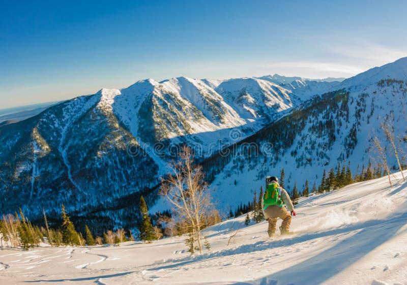 Snowboarder Freeride сползает вниз крутой склон на зоре стоковое изображение rf