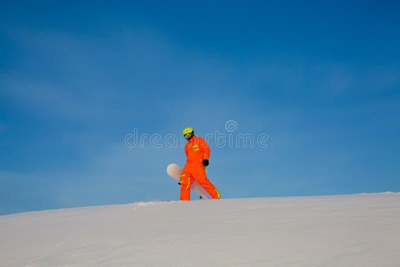 Snowboarder freerider met witte snowboard die zich op de bovenkant van de skihelling bevinden royalty-vrije stock afbeeldingen