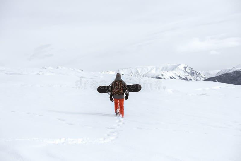 Snowboarder gaat de bergopwaartse bergen van de skireis royalty-vrije stock afbeelding