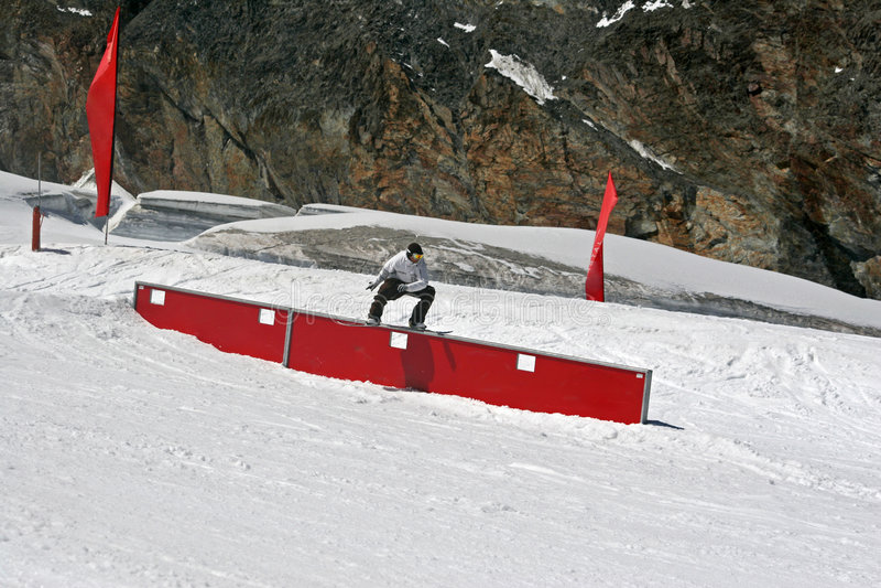 Snowboarder glissant sur un cadre image stock