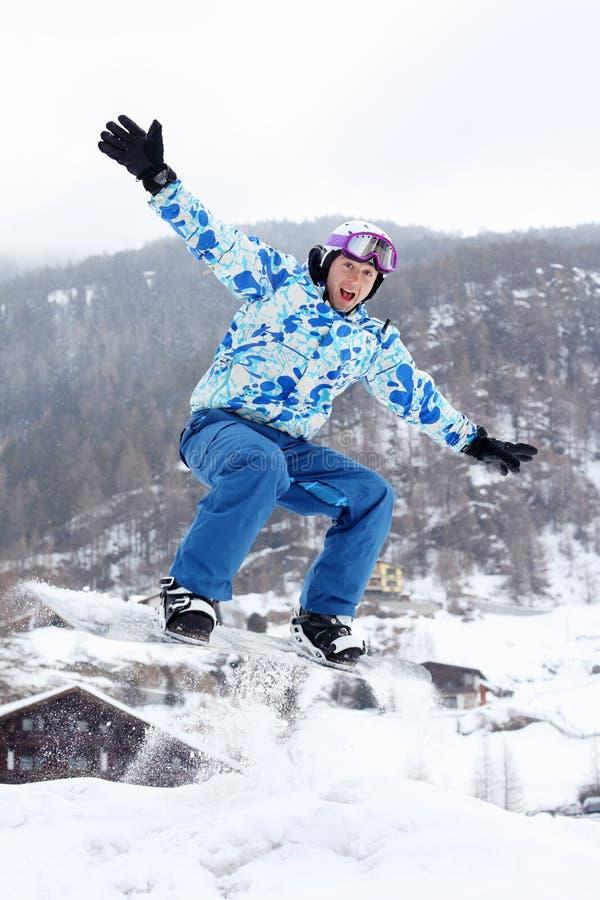 Snowboarder gritando em saltos do terno do esporte imagens de stock royalty free