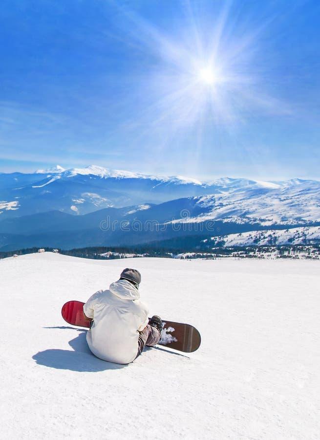 Snowboarder het ontspannen tegen bergen in zonstralen, wintersportenvakantie reist bij het concept van het skikuuroord stock fotografie