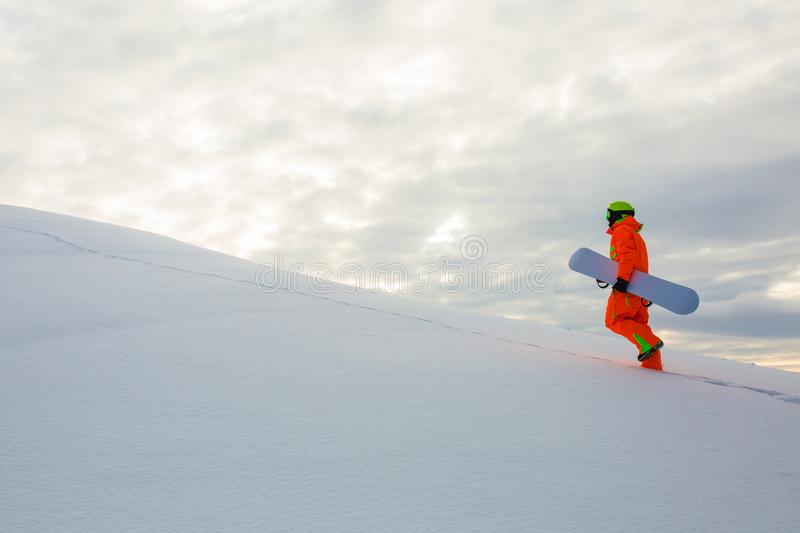 Snowboarder climbing on the top of ski slope royalty free stock photos