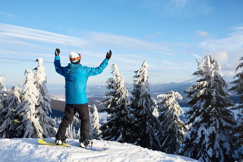 Snowboarder hob seine Arme und Hände zum Himmel am Skiort an Mann kletterte eine Gebirgsspitze durch Wald für lizenzfreie stockbilder