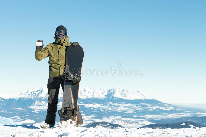 Snowboarder holding blank lift pass in one hand and snowboard in another with beautiful mountains on background royalty free stock photography