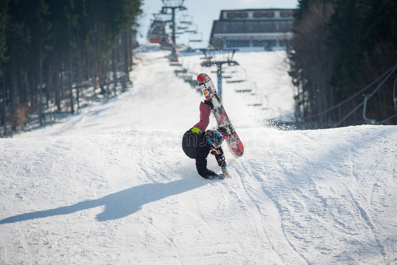 Snowboarder i ögonblicket av att falla på den snöig lutningen royaltyfri bild