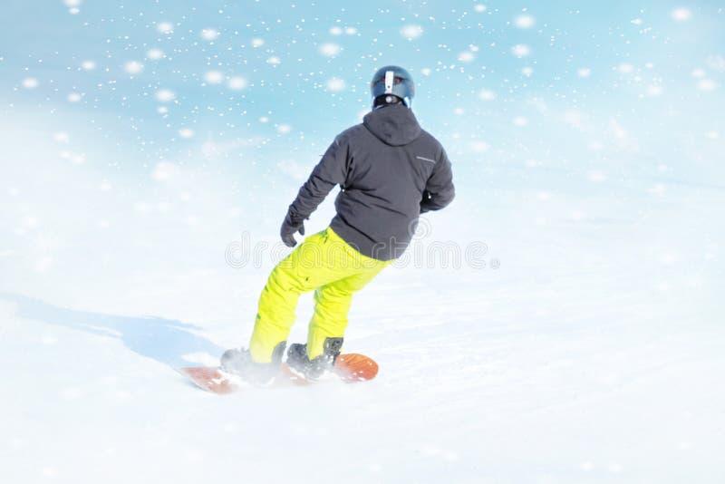 Snowboarder i den ljusa sportswearen som gör trick mot av härlig vinterbakgrund royaltyfria foton