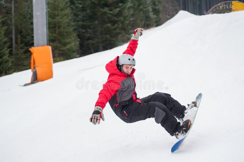 Snowboarder im Moment des Fallens auf die schneebedeckte Steigung stockfotografie