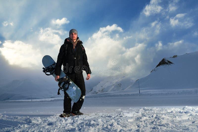 Snowboarder im schwarzen Anzug, der auf der Straße steht lizenzfreie stockbilder