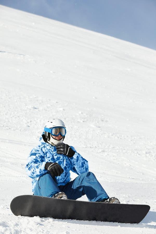 Snowboarder im Skianzug sitzt auf schneebedecktem Abhang stockfotografie