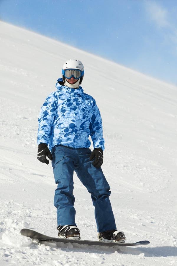 Snowboarder im Skianzug steht auf Snowboard lizenzfreie stockfotos
