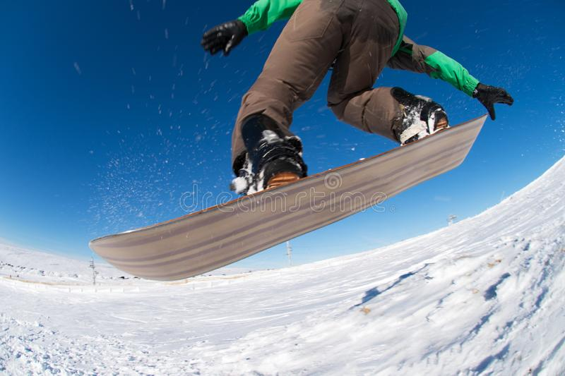 Snowboarder jumping against blue sky. Snowboarder executing a radical jump against blue sky royalty free stock photography