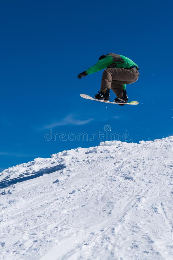 Snowboarder jumping against blue sky. Snowboarder executing a radical jump against blue sky royalty free stock image