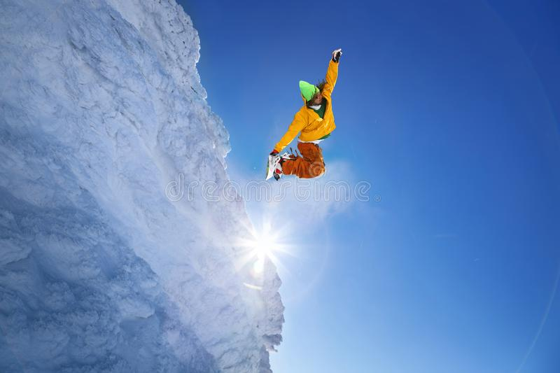 Snowboarder jumping against blue sky stock photography