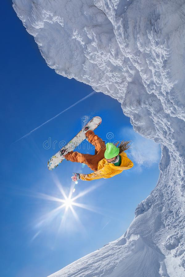 Snowboarder jumping against blue sky stock image
