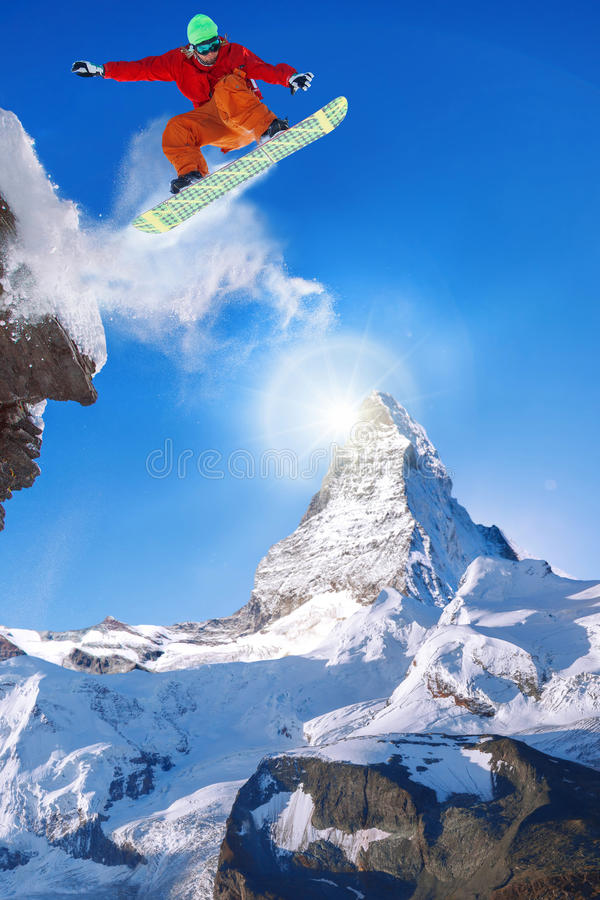 Snowboarder jumping against Matterhorn peak in Switzerland stock photography