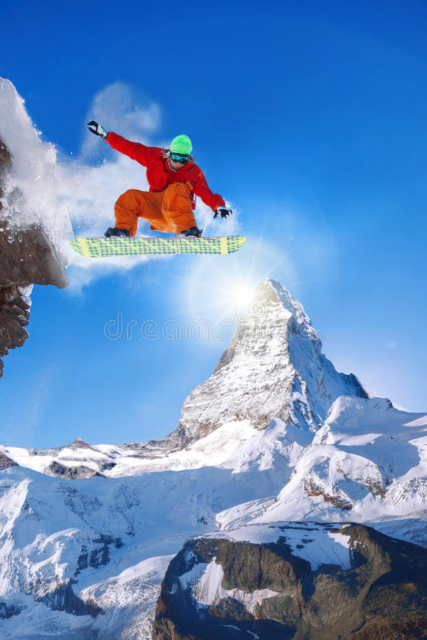 Snowboarder jumping against Matterhorn peak in Switzerland royalty free stock images