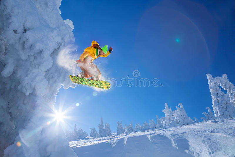 Snowboarder jumping against sunset stock images