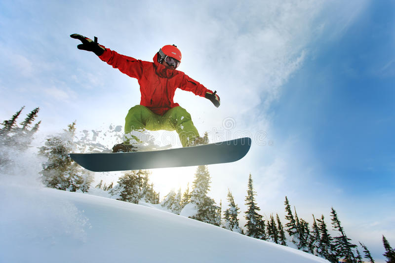 Snowboarder jumping. Through air with deep blue sky in background stock image