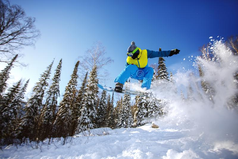 Snowboarder jumping from the springboard against the sky. Snowboarder jumping through air with deep blue sky in background royalty free stock photography
