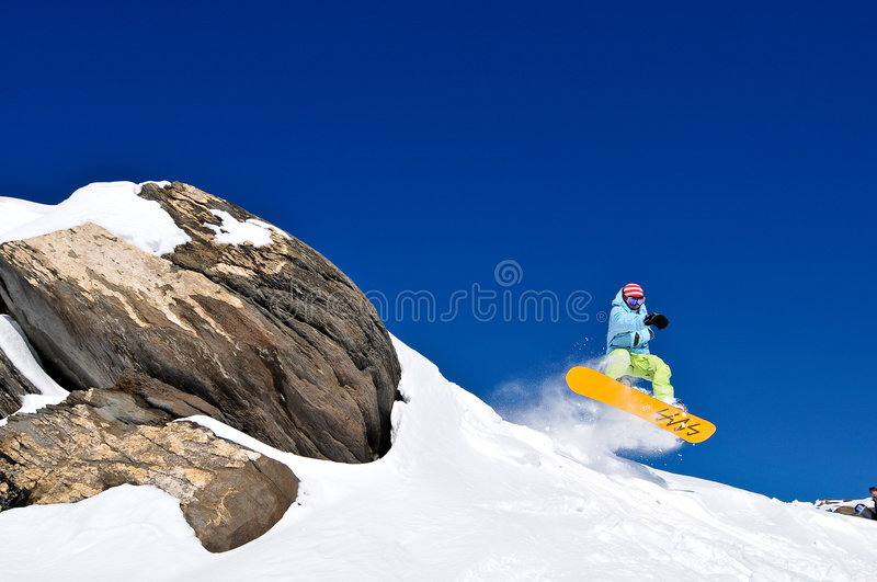 Snowboarder jumping of cliff at fresh snow stock image