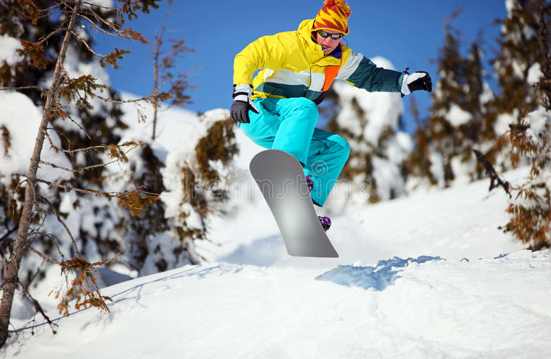 Snowboarder jumping on mountain slope stock photos