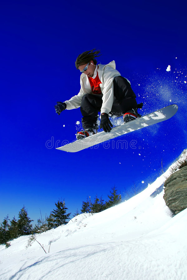 Snowboarder jumping over the rock stock images