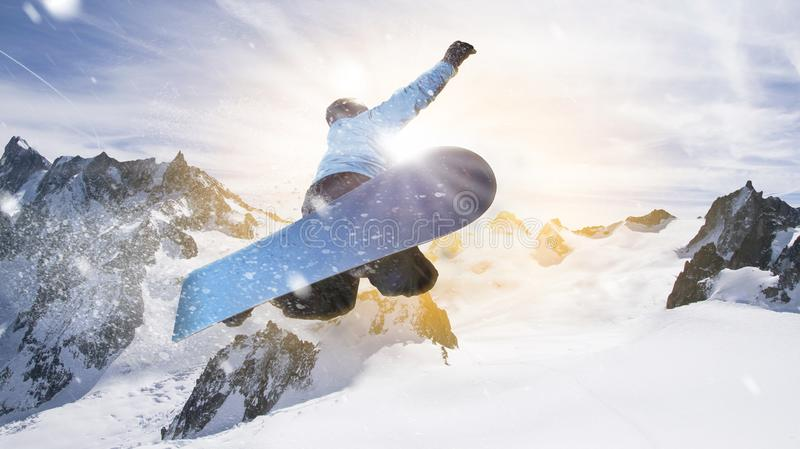 Snowboarder jumps through the air into the sunlight in dolomites alps royalty free stock photography